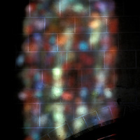Sunlight shines the stained glass colors of a church window in France casting a colorful projection on the interior wall.