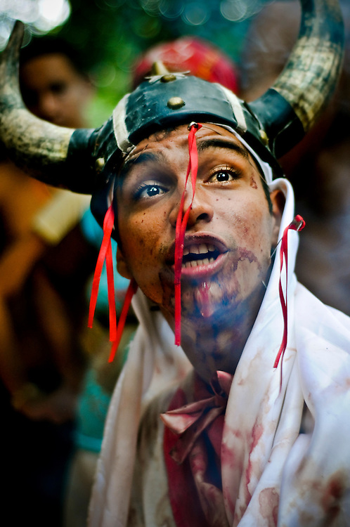 A man said to be possessed by a Viking spirit makes prophesies in a strange, growling voice to a group of Maria Lionza followers during their pilgrimage to Sorte mountain in Yaracuy, Venezuela. While possessed, the man partially cut his tongue, suck nails into his face and bled profusely, covering his white clothing with red stains.
