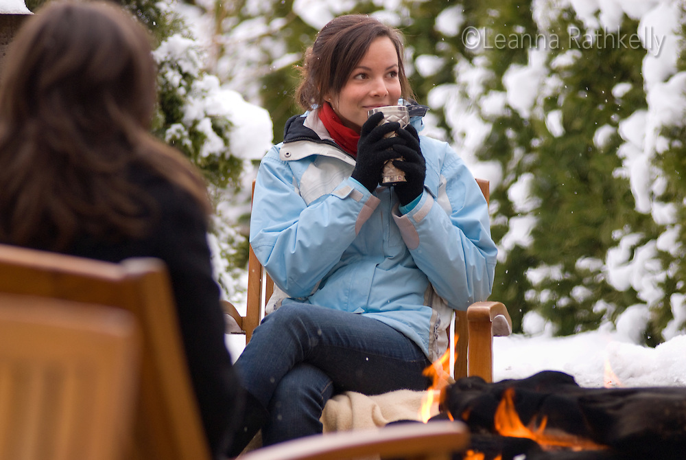 A teenage girl enjoys a hot drink in the winter snow by an outdoor fire.