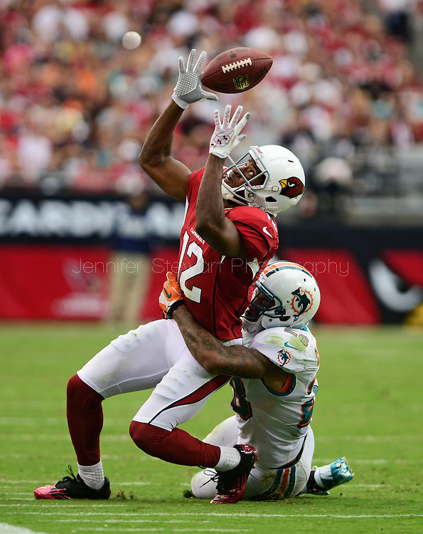 Sept. 30, 2012; Glendale, AZ, USA; Arizona Cardinals wide receiver Andre Roberts (12) attempts to make a catch against Miami Dolphins cornerback Nolan Carroll (28) in the second half at University of Phoenix Stadium. The Cardinals defeated the Dolphins 24-21 in overtime. Mandatory Credit: Jennifer Stewart-US PRESSWIRE.