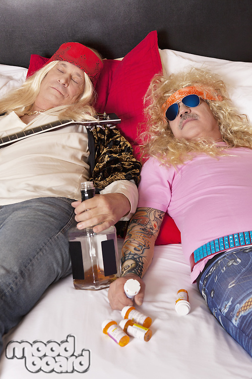 Two drunk male friends reclining on bed