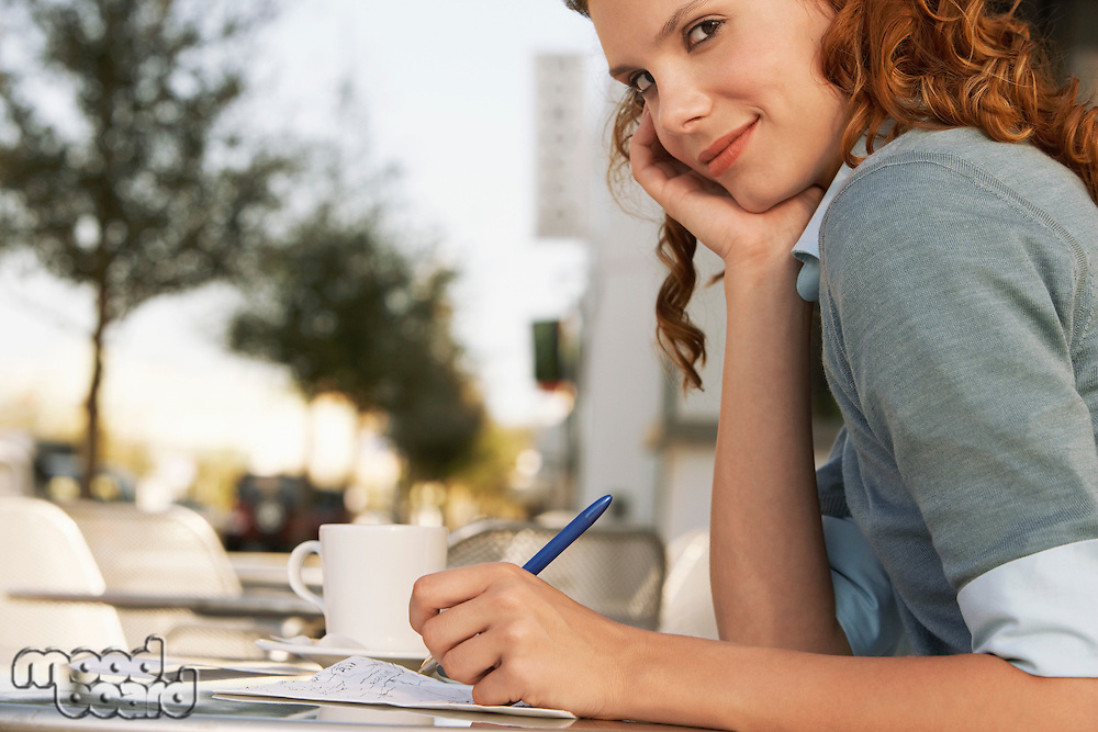 Young woman writing at outdoor cafe close-up