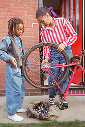 Mother and young son mending bicycle at front of house,