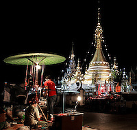 Night Market: The Buddhist temples form the background for the remnants of the night market as the vendors pack their goods away, Wat Chong Kham and Wat Chong Klang, Mae Hong Son Thailand.<br /> <br /> Brightly lit by flood lights and strings of electric lights, the Stupas of the Buddhist temples challenge the night sky.  A bright green umbrella reflects light down onto the vendor&rsquo;s stalls.