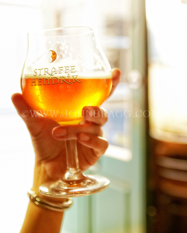 Photo of a patron enjoying a beautiful amber beer at 't Brugs Beertje, a beerhouse in Bruges, Belgium.