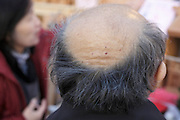 back view of balding and graying male person