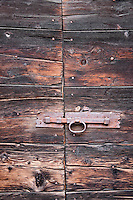 Ticino, Southern Switzerland. Old wooden door and metal latch. Lovely red weathered wood texture.