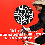 A cyclist passes a sign for  the 16th Busan International Film Festival, Busan, South Korea, October 6, 2011.