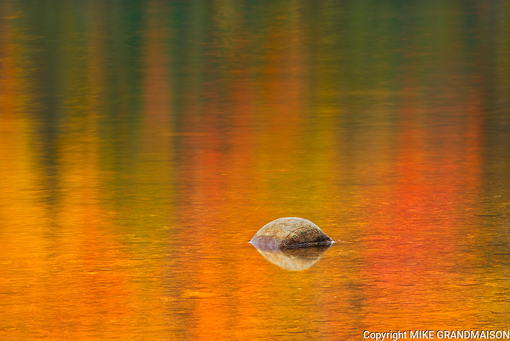 Rock and autumn  colors reflected in Lac Wapizagonke. Great Lakes - St.  Lawrence Forest Region.<br />