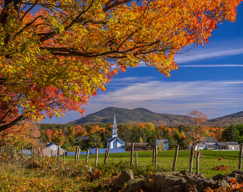 New England Village in fall, church, homes, barns, and pasture, framed by Maples with Mt Whittier background, Tamworth, NH