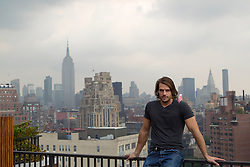 portrait of a man on a rooftop overlooking New York City