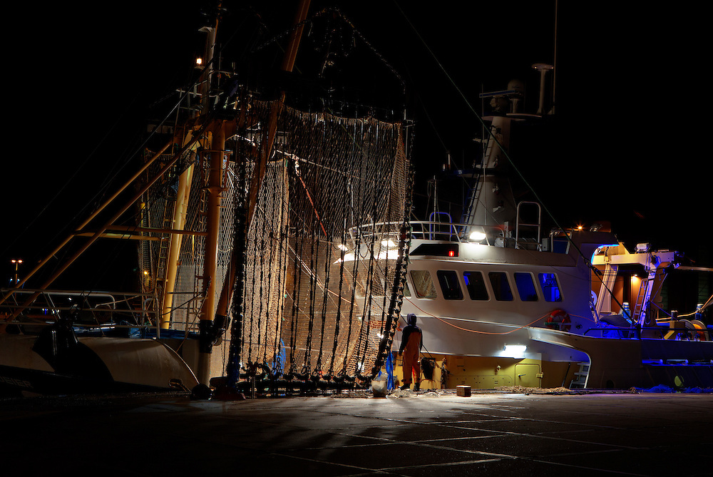 Fisherman taking a break while working on repairs to the pulse nets on the beam trawler 'Boeier' (SCH 18). Vlissingen, The Netherlands. <br /> <br /> Pulse nets emit an electrical pulse around the net which shocks fish out of the seabed, pushing them up into the net. <br /> <br /> It is claimed that pulse trawling causes less damage to the seabed and the fish caught than traditional beam trawling. <br /> <br /> The nets are also lighter, which leads to lower fuel costs, making this form of fishing very popular in some countries, although in others it remains controversial due to uncertainty about its impact on the marine ecosystem.