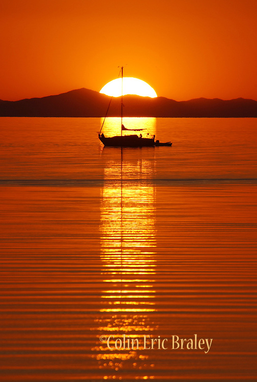 A sailboat is silhouetted as the sun sets on a warm summer day on the Great Salt Lake in Utah.