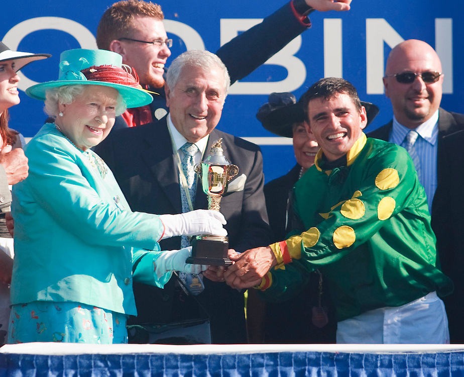 Queen Elizabeth II presents the 151st Queen's Plate trophy to Big Red Mike's owner Dom Romeo, centre, and jockey Eurico Rosa da Silva at Woodbine racetrack in Toronto, Canada, July 4, 2010. <br /> AFP/GEOFF ROBINS/STR