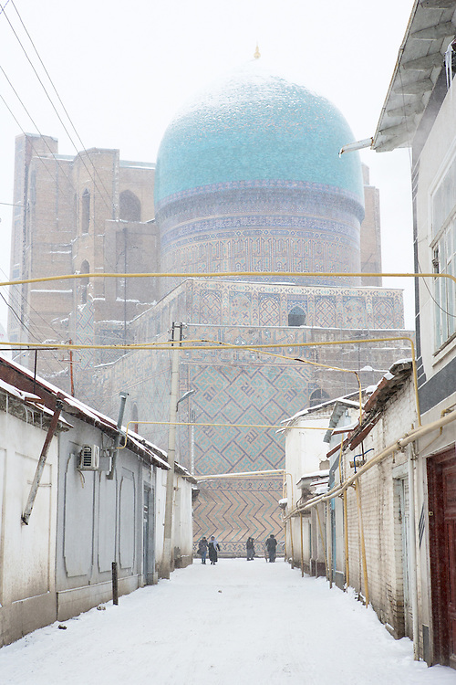 Snow on the Silk Road: people walk through a street in the old town leading up to the ancient Bibi-Khanym Mosque, Samarkand. Feb 5-6, 2014 saw a rare sustained snowy period in Samarkand, Uzbekistan, breaking record lows and resulting in school closures and power outages