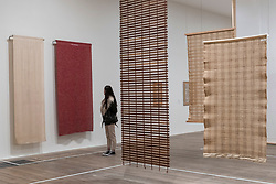 "© Licensed to London News Pictures. 09/10/2018. LONDON, UK. A visitor views (L) ""Drapery material woven for Rena Rosenthal's Madison Avenue store"", 1935, and (R) ""Free hanging room dividers"", 1949, all by Anni Albers.  Preview of the UK's first exhibition of works by German artist Anni Albers at Tate Modern who used the ancient art of hand-weaving to produce works of modern art.  Over 350 of her artworks from major collections from Europe and the US are on show 11 October to 27 January 2019.  Photo credit: Stephen Chung/LNP"
