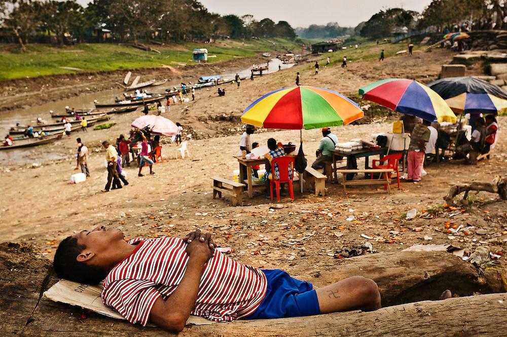 Colombia, Leticia, 2010. Esv&aacute;stica. <br /> Con la llegada de la tarde, baja la agitaci&oacute;n en el puerto de Leticia. Un trabajador del comercio descansa mientras las peque&ntilde;as embarcaciones provenientes del puerto principal descargan las &uacute;ltimas mercanc&iacute;as de la jornada. A un costado, el d&iacute;a cobra vida. El movimiento se traslada de la orilla del r&iacute;o a las calles h&uacute;medas de la zona urbana, cuando se comercializan los productos venideros del interior de la selva. Unas 40 mil personas habitan esta ciudad.<br /> With the arrival of the afternoon, there is less activity in the port of Leticia. A trade worker rests while the small boats from the main port unload the latest merchandise of the day. On one side the day comes to life. The movement from the shores of the river to the humid streets of the urban zone, where the products of made from the forest are traded. About 40,000 people inhabit this city.
