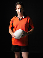 Rugby player standing holding ball portrait
