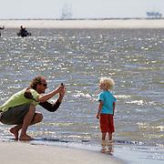 Nederland, Schiermonnikoog, 18-07-2010 Vader makt met zijn iPhone een foto op het Noordzeestrand op Schiermonnikoog.FOTO: Gerard Til / Hollandse Hoogte