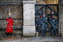 © Licensed to London News Pictures. 10/12/2017. London, UK. A member of the Household Cavalry and armed p[olice officers guard the entrance to Horse Guards Arch as snow falls over Horse Guards Parade in London on Sunday, 10 December 2017. Photo credit: Tolga Akmen/LNP