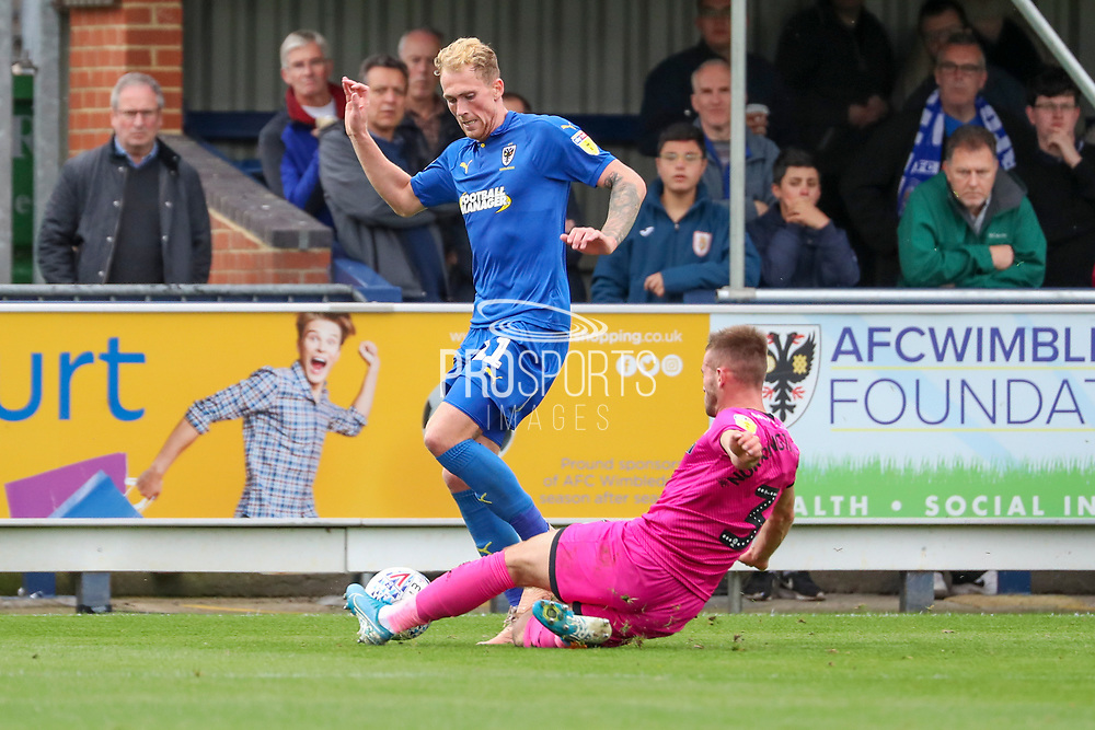 Rochadale defender Rhys Norrington-Davies (3) performing a slide tackle on AFC Wimbledon midfielder Mitchell (Mitch) Pinnock (11) during the EFL Sky Bet League 1 match between AFC Wimbledon and Rochdale at the Cherry Red Records Stadium, Kingston, England on 5 October 2019.