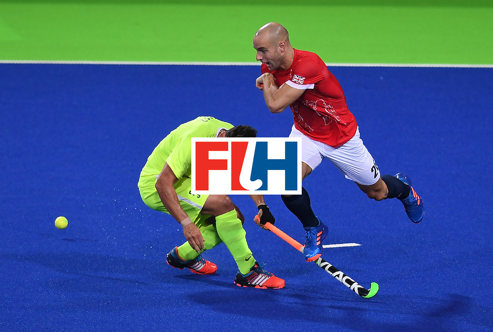 Brazil's Joaquin Lopez (L) dives as Britain's Nick Catlin jumps over him during the men's field hockey Brazil vs Britain match of the Rio 2016 Olympics Games at the Olympic Hockey Centre in Rio de Janeiro on August, 9 2016. / AFP / MANAN VATSYAYANA        (Photo credit should read MANAN VATSYAYANA/AFP/Getty Images)
