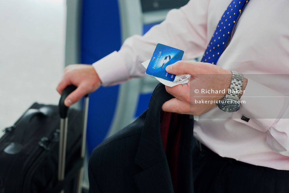 A businessman holds travel documents as he checks-in at the British Airways self-ticketing kiosk at Heathrow's terminal 5.