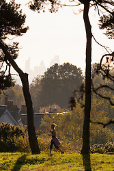 Hampstead Heath, London, October 28th 2014. A runner on Hampstead Heath enjoys the early morning sunshine.
