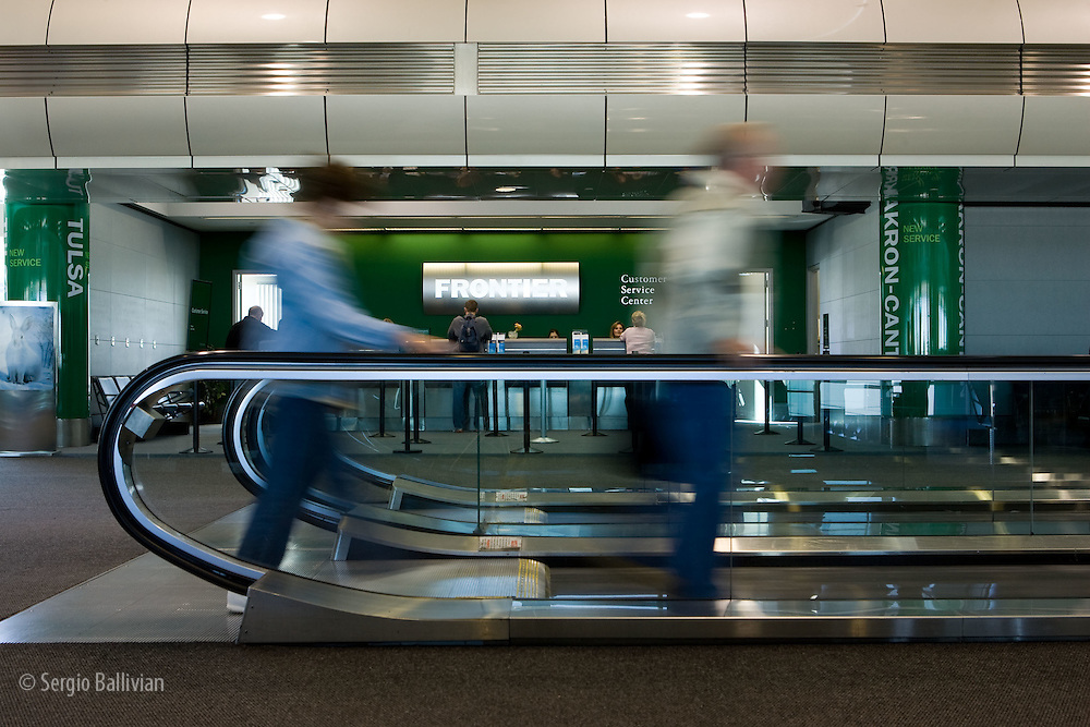 Travelers using moving walk way in front of Frontier Airlines at Denver International Airport.