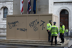 © Licensed to London News Pictures . 20/06/2015 . London , UK . Police alongside the Cenotaph on Whitehall , which is protected by graffitied wood boards . Tens of thousands of people march from the Bank of England to Parliament , to protest economic austerity in Britain . Photo credit: Joel Goodman/LNP