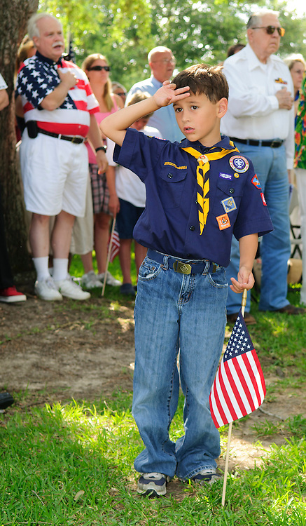 Cub Scout R.C. Bean, 8 salutes while holding an American flag during the dedication ceremony for the new Friendswood Veterans Memorial that was dedicated today.