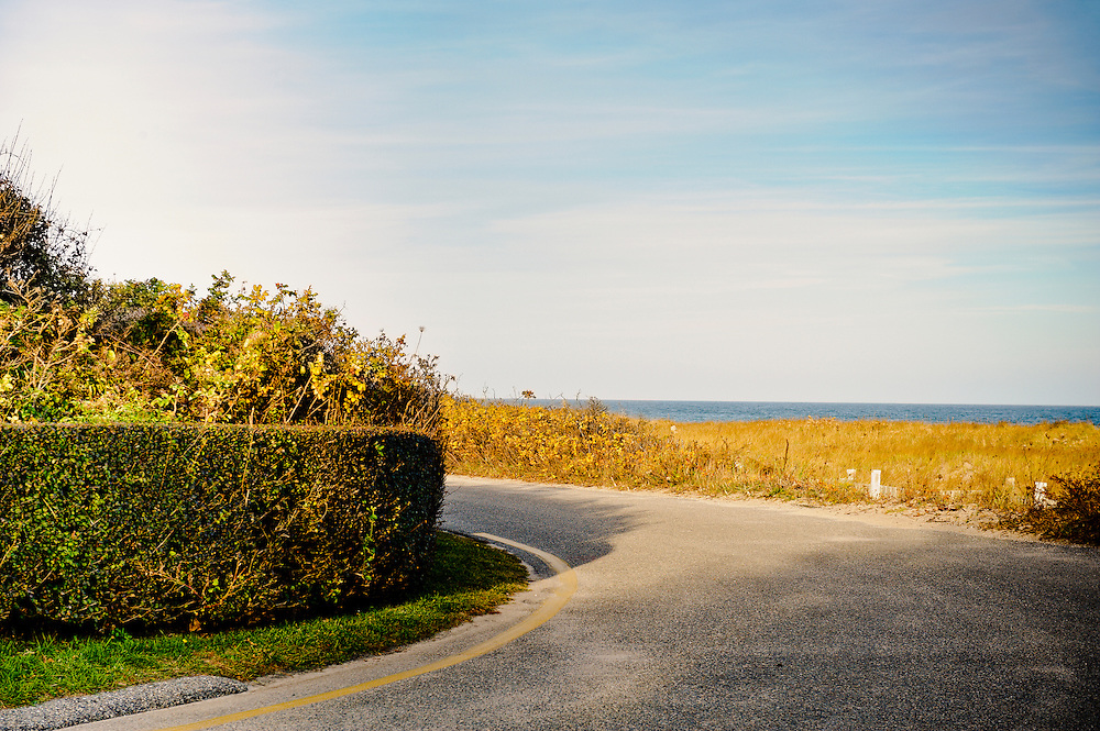 Country road with view of the ocean in the fall with clear blue sky and copy space, Nantucket, Cape Cod, Massachusetts, USA November 2010