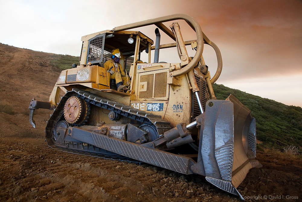 A bulldozer takes a quick break from cutting fire line during the La Brea fire. Bulldozer operators work through smoke and flame on steep hillsides, day and night. They are crucial for clearing wide fire breaks, but they are expensive and destructive and cannot be used in pristine wildland preserves.