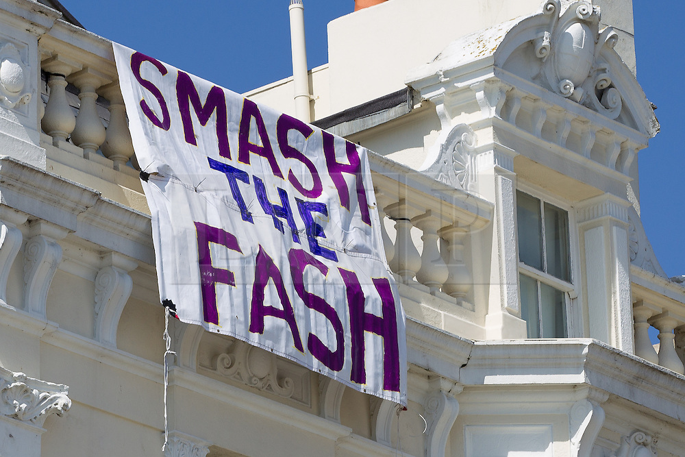 "© Licensed to London News Pictures . 21/04/2013 . Brighton , UK . A large banner reading "" Smash the fash "" is hung from a building on the seafront . Nationalist group March for England hold a march along Brighton seafront today (Sunday 21st April) . The group was supported by supporters of the English Defence League and opposed by anti fascist and left wing groups . The annual march takes place close to St George's Day and frequently results in scuffles and violence between opposing groups and police . Photo credit : Joel Goodman/LNP"
