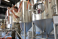 A brewmaster checks the clarity of his latest batch of beer at the Orlando Brewery in Orlando, Florida.