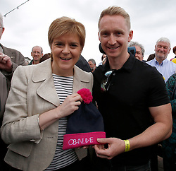 First Minister in Oban to visit SNP street stall and walkabout, George St, Oban.Pictured here receiving an Oban Live hat from Daniel Gillespie of Skerryvore....... <br /> (c) Stephen Lawson | Edinburgh Elite media