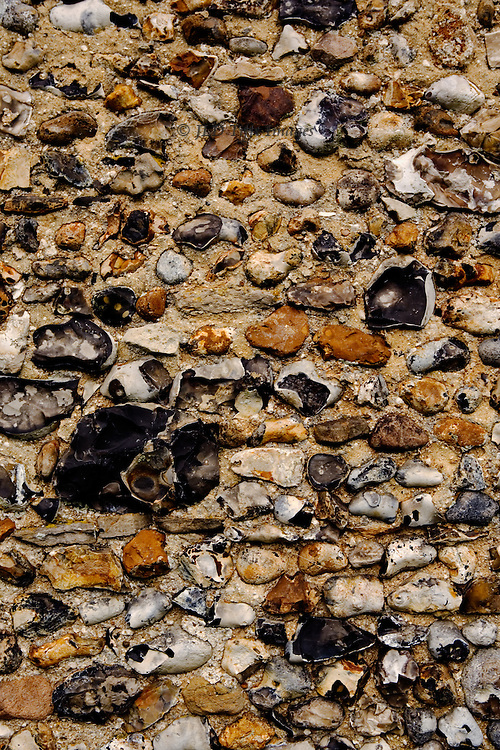 Flint and stone mortared wall of a church in Suffolk, England, in shades of black, grey, and yellow.