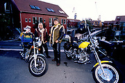 A biker couple both wearing sheepskin waitscoats and leather trousers, standing with two fancy motorbikes. Kristiansands Norway 2000