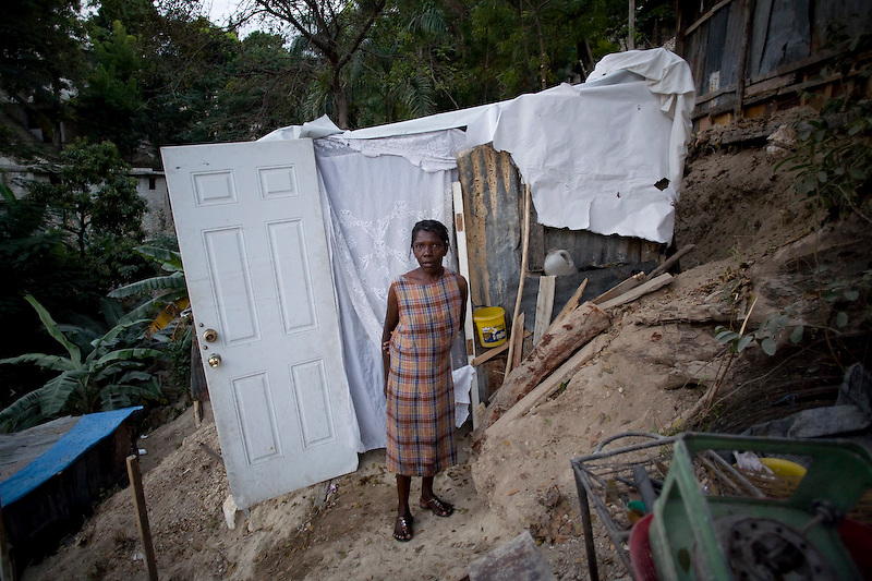 "Ida Phillip stands in front the shelter she and her son built. Six family members are living in this shelter built on a steep hillside. They lost thier home and most of their possesions in the earthquake and Ida say's ""I haven't recieved any food aid because I would have to fight for it"". Nerettes, Haiti. Photo by Ben Depp 2/8/2010"