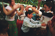 A boy dances with Garoafa Mihai (right of photo), whilst other girls dance and watch, in a tent on the day of the baptism of Sarion Bratu Badea. The party following the baptism was to last for 12 hours. In the Roma camp of Sintesti, near Bucharest.