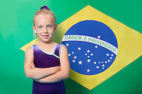 Portrait of a happy young female gymnast with arms crossed standing in front of Brazilian flag