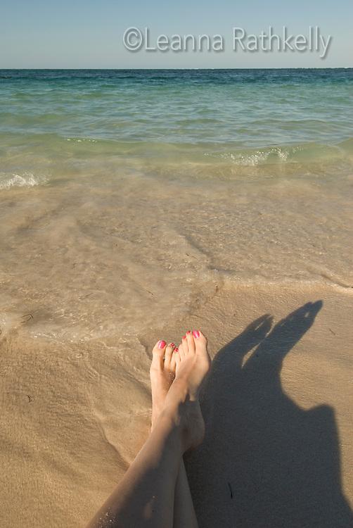 Legs relax on the white sand of Bavaro Beach, a popular tourist destination.