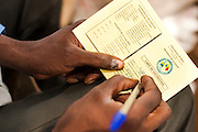 Vaccinator Bala Diakite fills in the vaccination card of a child getting vaccinated for the first time in the village of Banankoro, Mali on Saturday August 28, 2010.