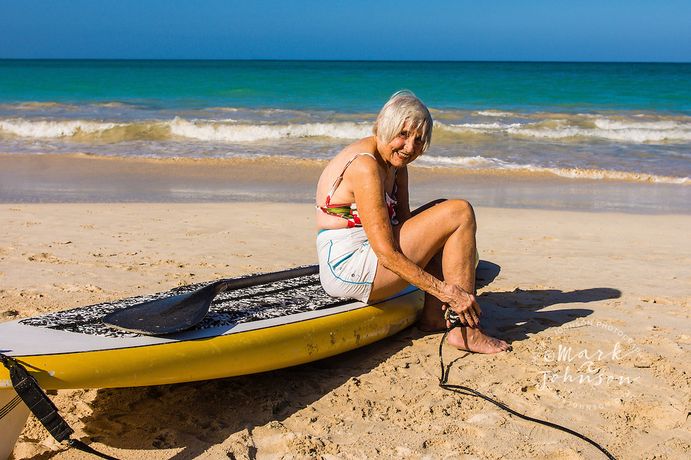 Older woman putting on leash for Stand Up Paddle Boarding, Kailua Beach, Oahu, Hawaii