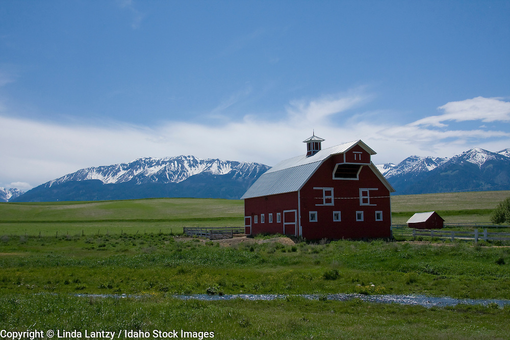 Oregon, Enterprise. A farm with barn sits beneath the snow capped mountains of the Wallowa Range of Northeast Oregon.