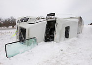 A semi truck lies on its side in the median along Interstate 80 in Poweshiek County in Iowa on Wednesday February 2, 2011.