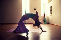 Woman artfully practicing the heart felt yoga pose Wild Thing in a moody studio atmosphere. AKA CAMATKARASANA