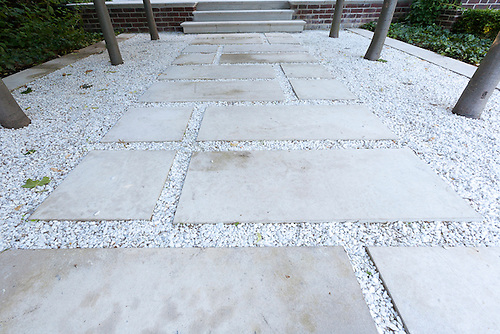 A Garden Pathway Made Form Square Cut Limestone Stepping Stones Laid On  White Marble Chips.