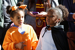 Donning Halloween costumes Nia Mensah, Jolie Mensah of Glenside, PA wait at the platform to welcome Harry Potter.