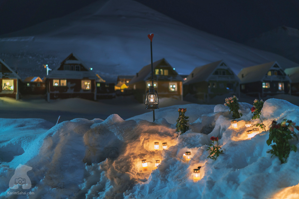On 'Vei 230' street in Longyearbyen (Svalbard), flowers and candles are placed in the snow to commemorate the victims of an avalanche which destroyed nine homes and claimed two lives. On December 19 2015 at around 11am, more than 5000 tons of snow tumbled down towards the town, moved many houses off their foundations, flipped cars, and buried residents under several meters of snow. The avalanche took place the day after a massive storm hit the Arctic archipelago. It was the fiercest ever recorded in Svalbard, with winds reaching 100 kph. Today, calm has regained the area, families celebrate Christmas but the area beneath Sukkertoppen has been evacuated and the snow cover remains under watch.